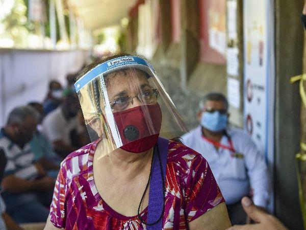 मुंबई में एक वैक्सीनेशन सेंटर के बाहर टीका लगवाने पहुंची महिला।