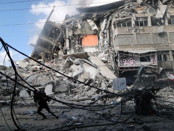 इजराइली एयरफोर्स की बमबारी में गिरी बिल्डिंग और जान बचाकर भागता फिलिस्तीनी युवक। - Dainik Bhaskar