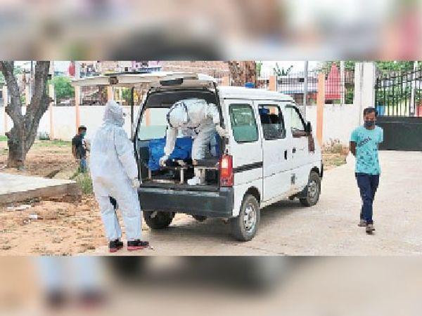 जीएनएम अस्पताल में कोरोना से मरे शव को एंबुलेंस में रखते कर्मी - Dainik Bhaskar