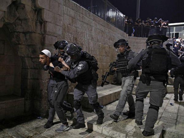 यरूशलम में एक फिलीस्तीनी युवा को हिरासत में लेकर जाती इजराइली पुलिस।