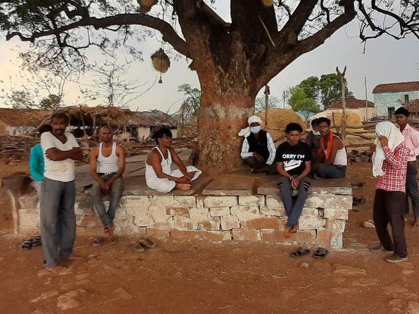 उनारीखेड़ी गांव में चबूतरे पर बैठे लोग। ये लोग बाहरी लोगों को रोकने के लिए बैठे हैं। हालांकि मास्क किसी ने नहीं लगाया है।