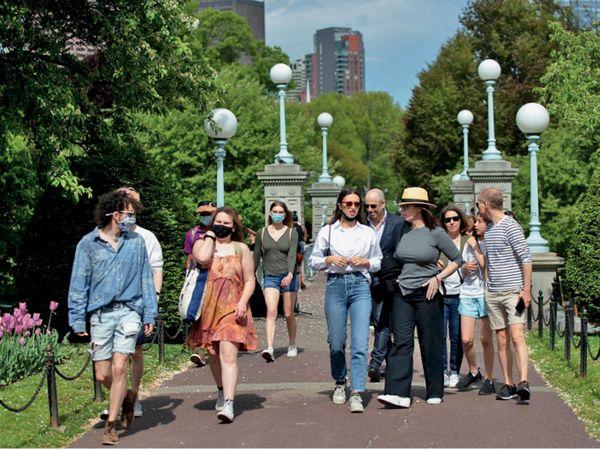 बोस्टन में शुक्रवार को एक पार्क में घूमते लोग। - Dainik Bhaskar