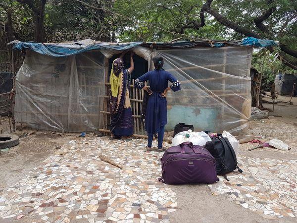 प्लास्टिक बांधकर झोपड़ी को सुरक्षित करता एक परिवार।