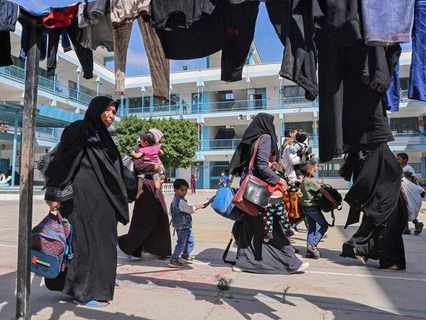 गाजा सिटी में करीब 40 हजार लोग बेघर हो चुके हैं। इन्हें शेल्टर होम या रिफ्यूजी कैम्प्स में रखा गया है। सोमवार को इन्हीं में जातीं महिलाएं और बच्चे।