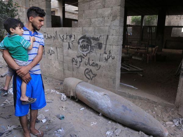 सोमवार को गाजा सिटी में इजराइल द्वारा दागा गया एक बम फटा नहीं, एक व्यक्ति इस बम को देखते हुए।