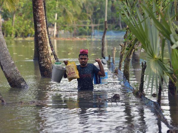 तस्वीर साउथ 24 परगना की है। यहां तूफान के बाद तेज बारिश से जगह-जगह पानी भरा गया। इस दौरान एक शख्स सामान लादकर सुरक्षित स्थान पर जाता हुआ।
