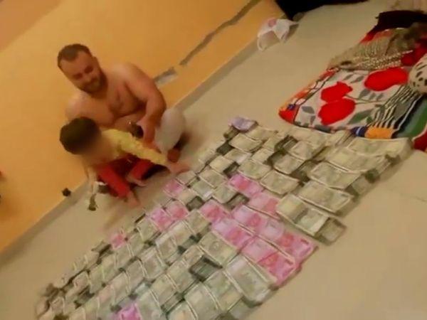 सोशल मीडिया जो वीडियो वायरल हो रहा है उसमें एक शख्स की गोद में एक बच्चा बैठा हुआ है और उसके आसपास पैसे पड़े हुए हैं। - Dainik Bhaskar