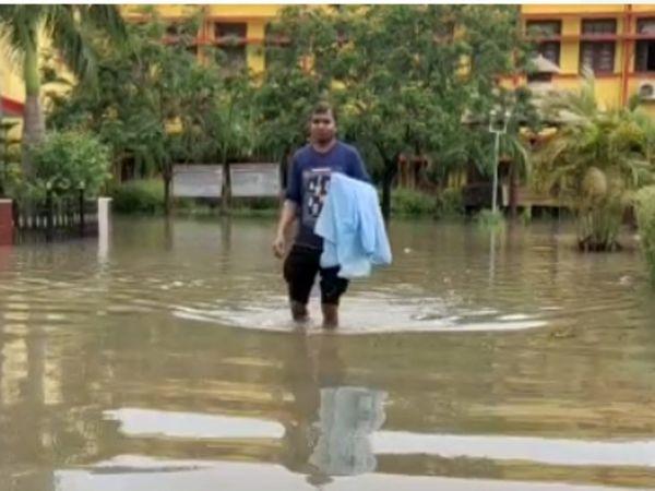 घुटने भर पानी में अस्पताल से बाहर आता कर्मी।