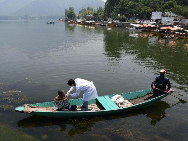 जम्मू-कश्मीर की राजधानी श्रीनगर में शनिवार को डल झील में नाव चलाने वालों के लिए खास वैक्सीनेशन ड्राइव चलाई गई। टीम ने शिकारा चलाने वालों को उनकी नाव में जाकर कोरोना का टीका लगाया। - Dainik Bhaskar