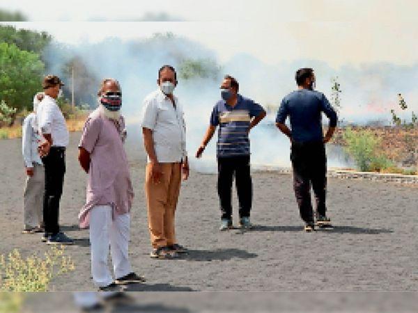 रनिंग ट्रैक के पास पौधों की देखभाल और अनावश्यक खरपतवार जलाते ग्रामीण एवं स्कूल स्टाफ। - Dainik Bhaskar