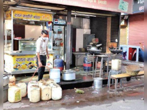 स्टेशन रोड पर अपनी दुकानों पर साफ-सफाई करते दुकानदार। - Dainik Bhaskar