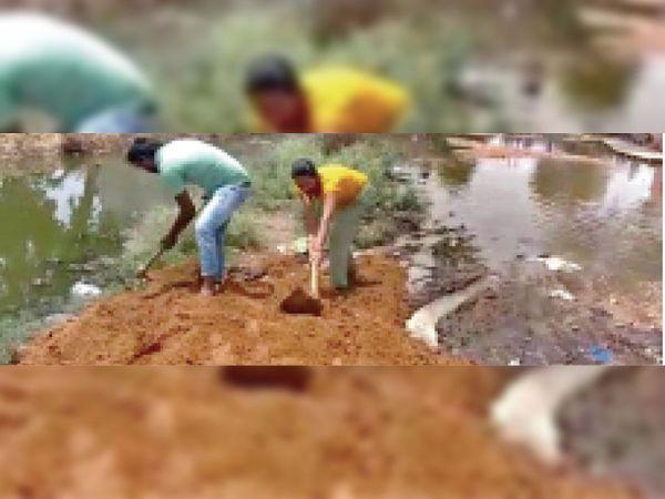 अंबाह में जग्गा राेड पर मिट्टी का भराव करते स्थानीय लाेग। - Dainik Bhaskar