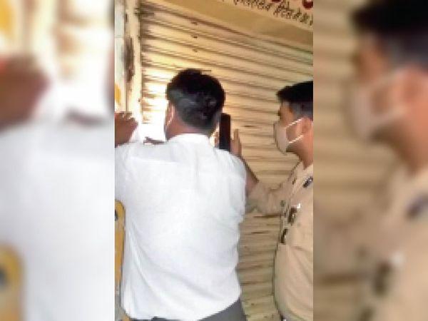 कोरोना नियम का उल्लंघन कर दुकान खोली, सील करते अधिकारी। - Dainik Bhaskar