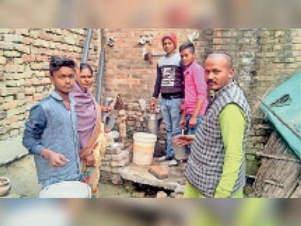 वैनी पंचायत स्थित वार्ड 13 में एक हैंडपंप से पानी लेते लोग। - Dainik Bhaskar