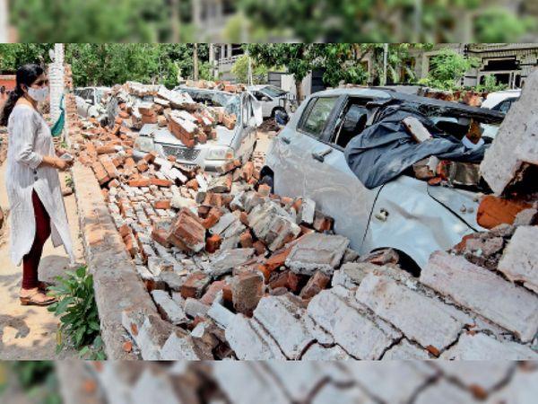 सेक्टर-9 में शनिवार रात तेज आंधी चलने से एक दीवार साथ खड़ी गाड़ियों के ऊपर गिर गई। क्षतिग्रस्त हुई अपनी गाड़ी को देखती एक महिला। - Dainik Bhaskar