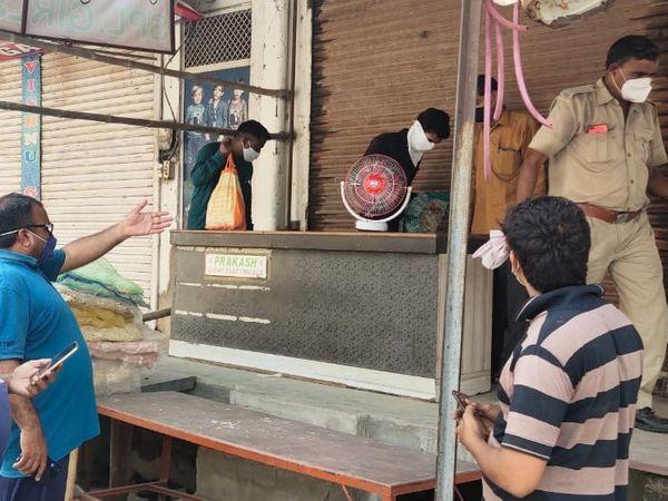 अलवर शहर में दुकान सील की कार्रवाई करते अधिकारी। - Dainik Bhaskar