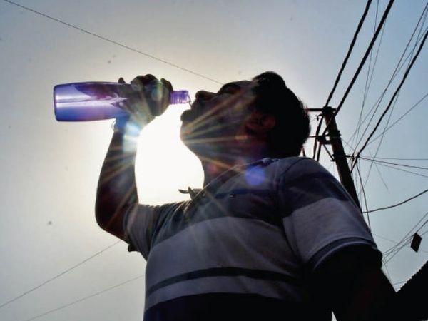 दिल्ली राेड पर दाेपहर में गर्मी से बचने के लिए पानी पीते हुए युवक। - Dainik Bhaskar