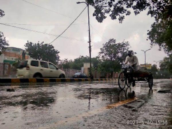 भिवानी. बारिश के दौरान सरकुलर रोड से गुजरता एक रेहड़ी चालक। - Dainik Bhaskar