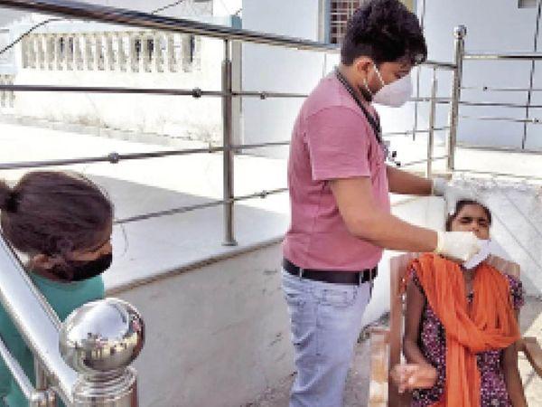 मनीषा के कोरोना सैंपल लेती मेडिकल टीम। - Dainik Bhaskar