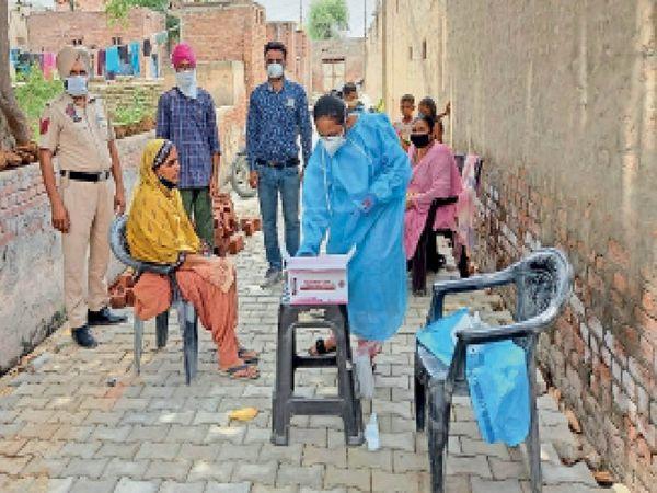 कोहाला गांव में लोगों के कोरोना सैंपल लेते स्वास्थ्य विभाग के कर्मचारी। - Dainik Bhaskar