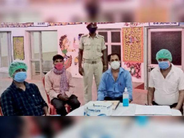 रेलवे स्टेशन पर कोविड टेस्ट के लिए यात्रियों का निबंधन करते कर्मी। - Dainik Bhaskar