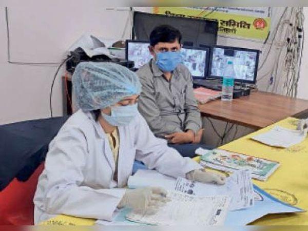 कोविड केयर सेंटर में मरीजों को दवाई लिखती एएनएम। - Dainik Bhaskar