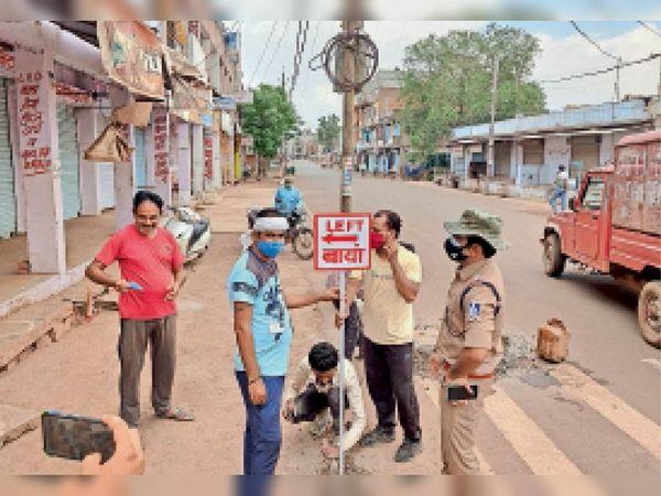 शिवपुरी शहर में 1 जून से बाजार खुलने की सूचना पर कोर्ट रोड पर दुकान खोलने के बोर्ड लगाते नगर पालिका के कर्मचारी व ट्रैफिक प्रभारी। - Dainik Bhaskar