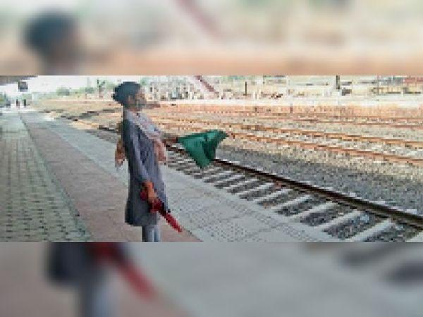 रेलवे स्टेशन पर ट्रेन को झंडी दिखाती महिला पोंट्समेन। - Dainik Bhaskar
