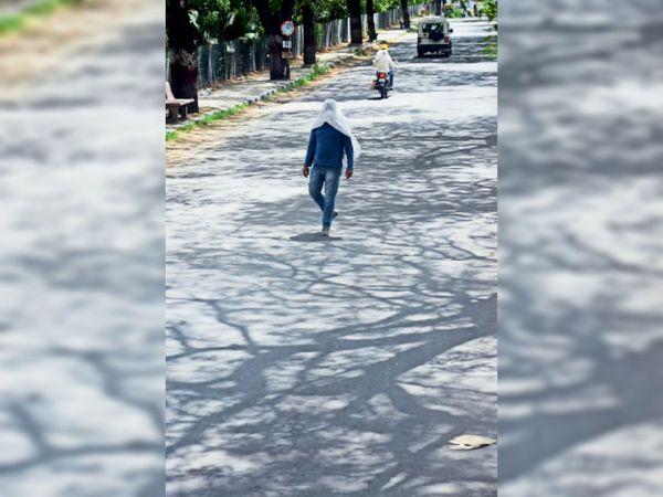पुलिस लाइन रोड पर गर्म हवाओं के थपेड़ों से बचाव के लिए व्यक्ति गमछा लपेटने के साथ ही छांव-छांव में चलता नजर आया। - Dainik Bhaskar