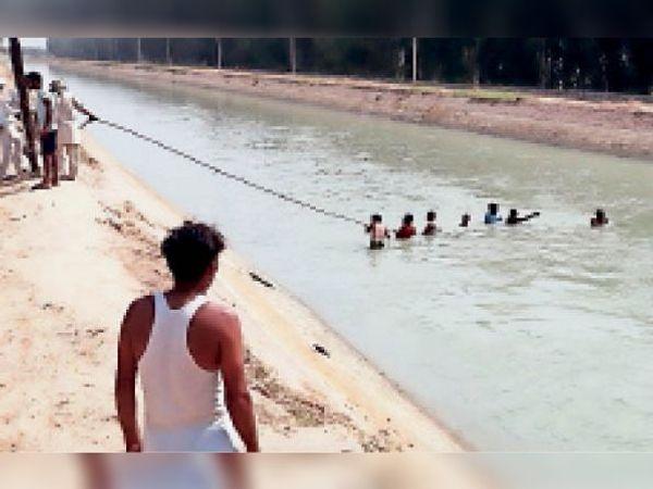 टोहाना। नहर में बहे युवक की रस्से की मदद से तलाश करते उसके परिजन। - Dainik Bhaskar