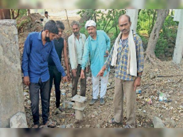 मांडू. आंबापुरा के बंद हैंडपंप काे बताते ग्रामीण। - Dainik Bhaskar