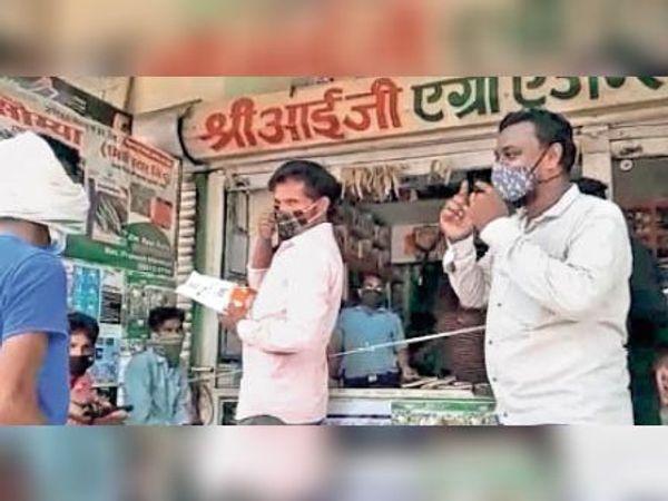 खाद-बीज दुकान पर गमछे की जगह मास्क लगाने की समझाइश देते सदस्य। - Dainik Bhaskar