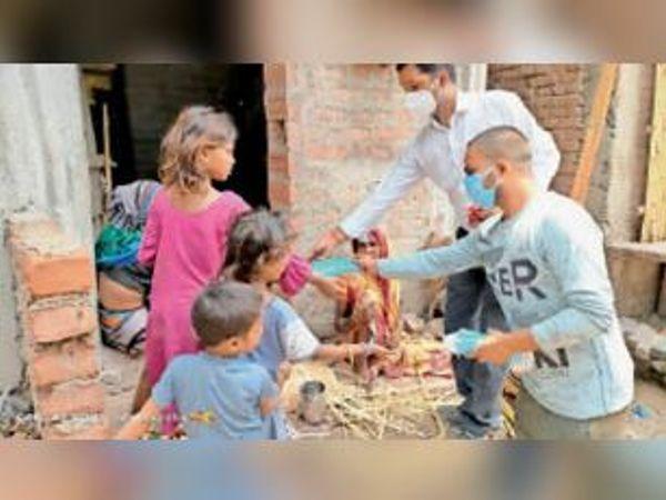 गरीब परिवारों के बीच मास्क वितरण करते भाजपाई। - Dainik Bhaskar