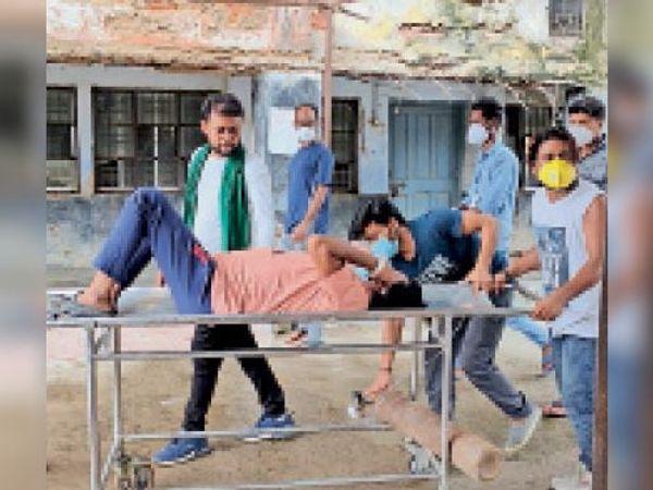 यह दृश्य डीएमसीएच के इमरजेंसी कैंपस का है। कोरोना आइसोलेशन वार्ड में भर्ती समस्तीपुर के इस मरीज को रविवार को सीटी स्कैन के लिए जाना था। मगर ट्रॉली मैन कोरोना मरीज होने पर इंकार कर दिया। उसके परिजन को खुद ट्रॉली लेकर जाना पड़ा।फोटो। राहुल कुमार गुप्ता - Dainik Bhaskar