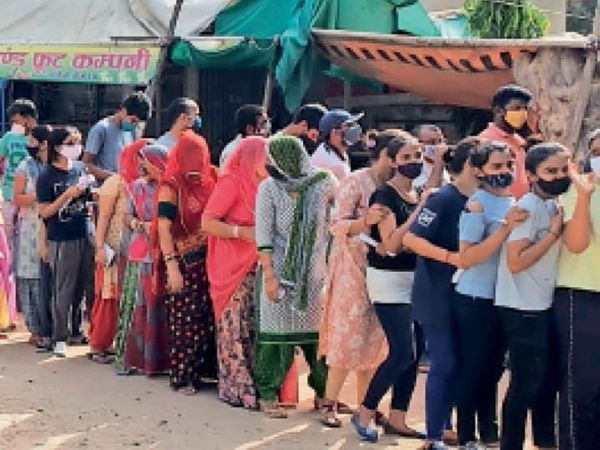 चिड़ावा. टीका लगवाने के लिए डालमिया स्पोर्ट्स कॉम्प्लेक्स के बाहर स्टेशन रोड पर लाइन में खड़ी महिलाएं व युवतियां। - Dainik Bhaskar