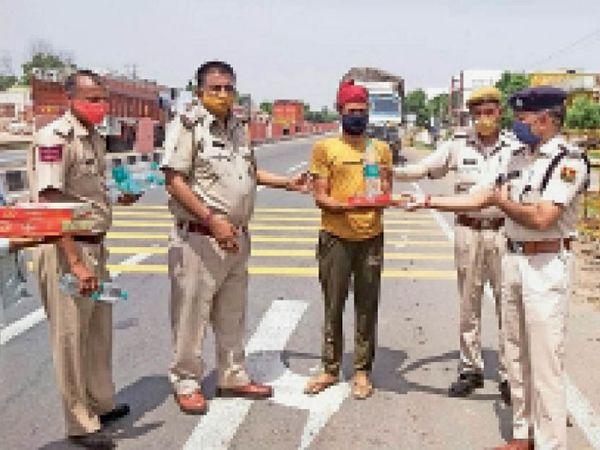 नेशनल हाइवे पर मानपुर थाने के बाहर ट्रकों को रोककर चालकों को खाने के पैकेट वितरित करते पुलिस अधिकारी व जवान। - Dainik Bhaskar