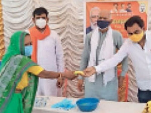 दंदरौआ मंडल के सदस्य गाता केंद्र पर ग्रामीणों को फल देते भाजपाई । - Dainik Bhaskar