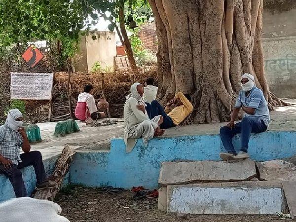 गोहद के सुहास गांव में ग्रामीण मास्क और गमछा बांधकर पेड़ के नीचे दूर-दूर बैठकर बात करते हुए । - Dainik Bhaskar
