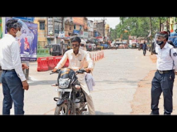 कोरोना कर्फ्यू के बीच घरों से निकलने वालों से पूछताछ करती पुलिस। - Dainik Bhaskar