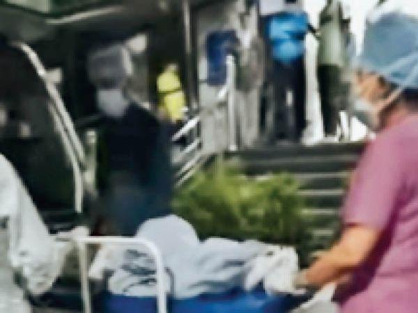 12 वर्षीय बेटी का शव परिजनों को सौंपते हुए अस्पताल का स्टाफ। - Dainik Bhaskar