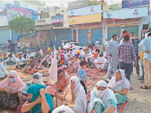 पुलिस स्टेशन मेन चौक मल्लांवाला के बाहर धरना देते मृतक किसान के परिजन। - Dainik Bhaskar