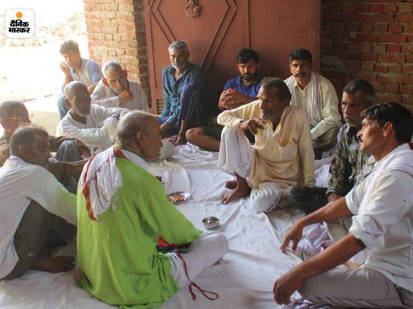 मुकटपुर गांव में मृतक मनोज के घर शोक जताने बैठे ग्रामीण, बीच में मृतक के पिता।