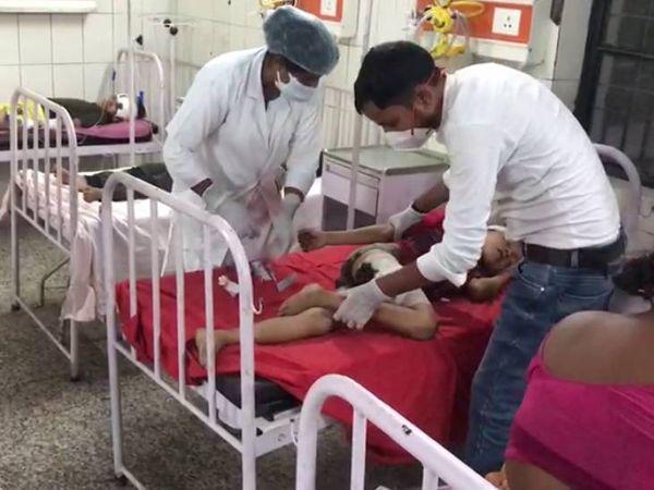 जिला अस्पताल में बच्चे का इलाज करता मेडिकल स्टॉफ।