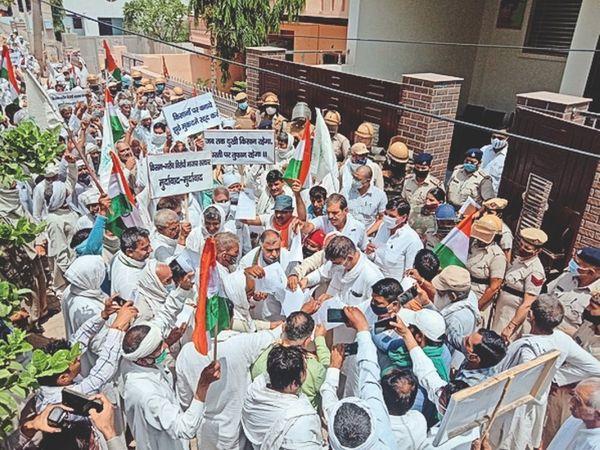 भाजपा सांसद धर्मबीर सिंह के आवास के बाहर तीन कृषि कानूनों की प्रतियां जलाते किसान।