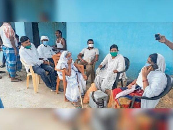 बैठे स्वास्थ्यकर्मी और आक्रोशित ग्रामीणों को समझाते मुखिया सीताराम दांगी। - Dainik Bhaskar