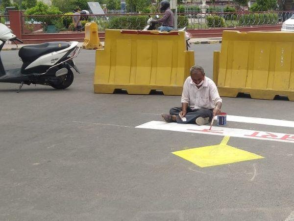 अलवर शहर में नंगली सर्किल पर स्लोगन लिखता व्यक्ति। - Dainik Bhaskar