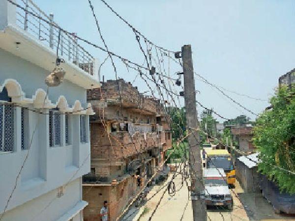 हकाम में सड़क किनारे बिजली के तार में बांधी गयी ईंट। इस खंभे में हुकिंग का जंजाल है। - Dainik Bhaskar