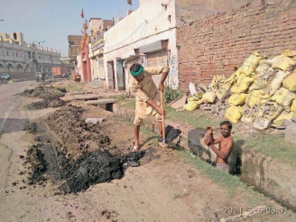 भिवानी. सरकुलर रोड पर कमला नगर के पास नाले  से कचरा निकालते मजदूर। - Dainik Bhaskar