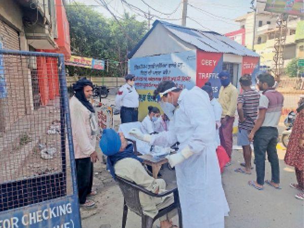 बाजार में घूम रहे लोगों के कोरोना टेस्ट करती स्वास्थ्य विभाग की टीम। - Dainik Bhaskar