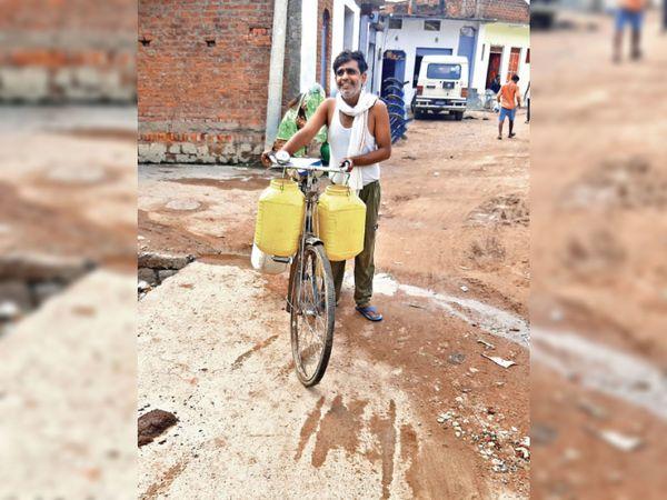छतरपुर/लवकुशनगर| चिलचिलाती धूप में साइकिल में डिब्बे टांग पर पानी भरकर लाता वार्डवासी। - Dainik Bhaskar